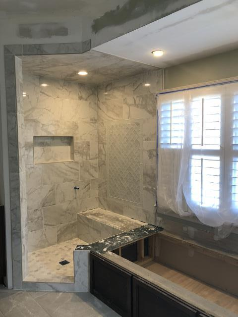 Vestavia Hills, AL - Can't wait to see the fantasy brown quartzite tub deck and glass enclosure that will finish out this large format marble tile shower with arabesque mosaic detail and custom cabinetry tub skirt for the undermount soaking tub.