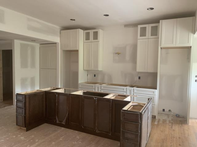 Birmingham, AL - Cabinets are being installed in this Riverchase kitchen. You will notice what looks like two refrigerators but one is a fridge and the other a freezer! A really neat way to get the amount of storage you need as well as the symmetry created in this particular layout. Symmetry was very important to the homeowner. The cook top will be installed along the wall with a gorgeous decorative hood and the island features a sink centered on the island which is centered on the cooktop. The pantry and double ovens are tucked away in a nook which leads to the laundry and larger walk-in pantry.