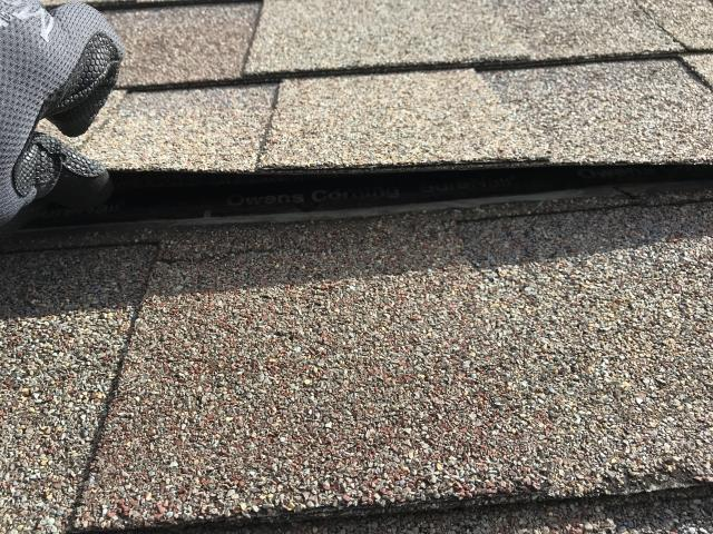 Symptom of wind damage is the loss of seal on the shingles.  They should not be able to be lifted easily as you see here.  High winds may cause debris to come under the shingle and keep it from sealing down as designed.  This is why you get a professional to inspect the roof!