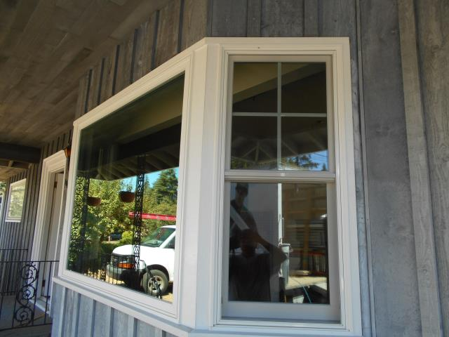 Milwaukie, OR - Installing five windows and two 2 panel doors with four sidelights. Three white windows with white hardware in living room will replace five casements currently arranged in a bay window; Double hungs on each end and one picture replacing three casements in the middle.