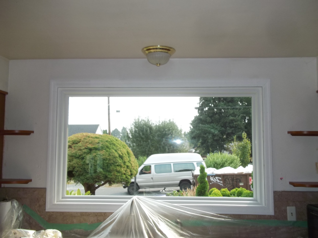 Replaced 6 storm windows with fibrex windows. Photo of large picture windows white interior/exterior.