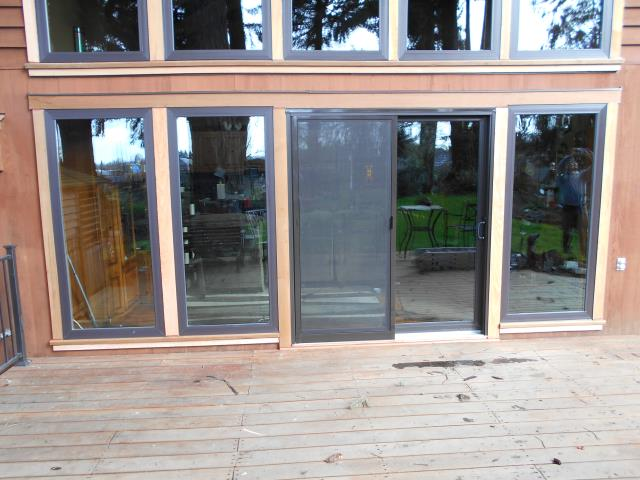 Lebanon, OR - We installed 22 replacement windows in this gorgeous home including this gorgeous sun room where they layered picture windows to welcome in the warm sun. We also installed 2 sliding glass doors for this beautiful place in Lebanon!