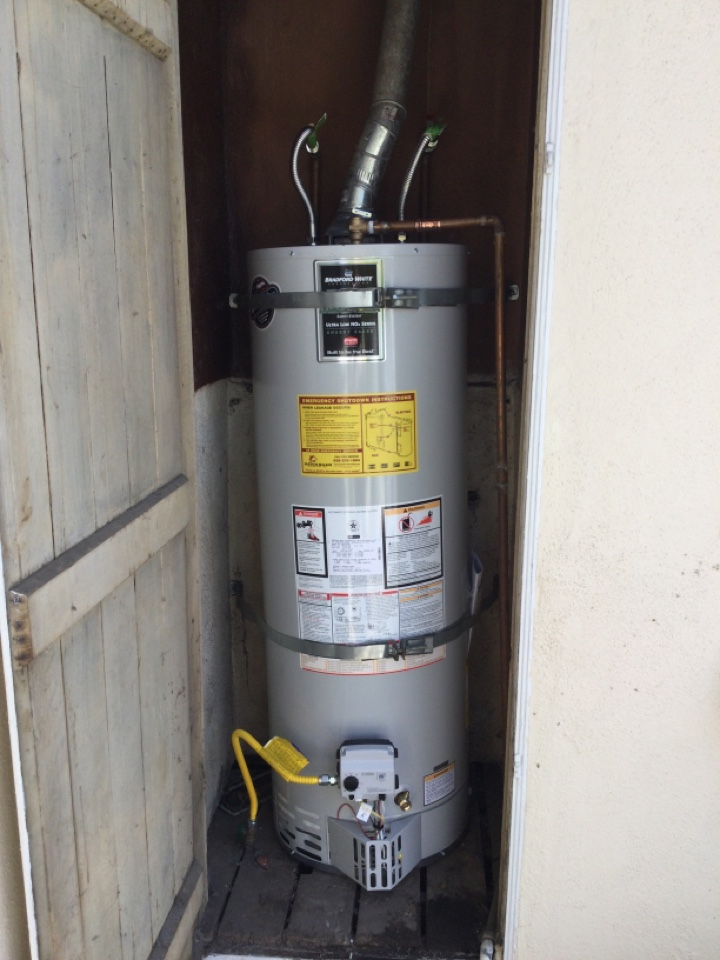 Plumber working on replacing Bradford White 50gallon residential water heater that was leaking in outdoor cabinet.