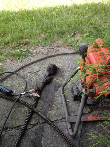 Unclog building sewer with electric snake and pulled back roots.