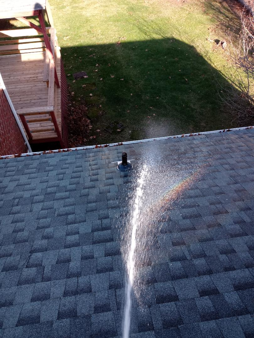 West Haven, CT - Hose testing this roof leak in West Haven Connecticut appears that one of the vent pipes is leaking.