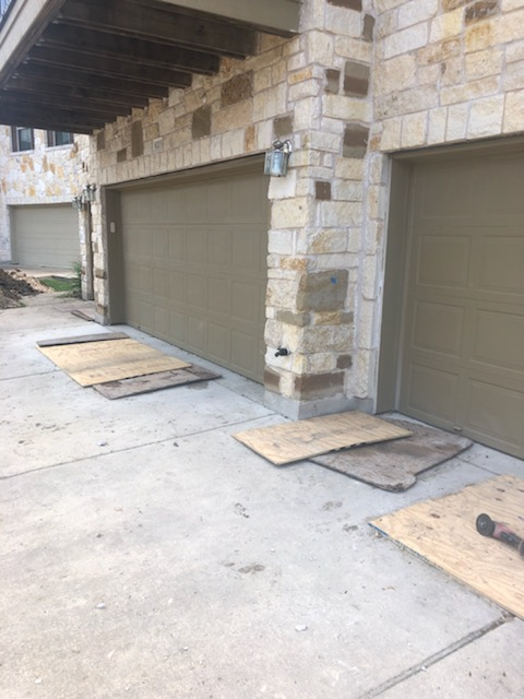 Austin, TX - Here is another section of the condominium we are doing a foundation repair on. These breakouts, or piers that are installed by breaking thru concrete, are temporarily covered with wood boards for safety reasons. Under each board is a hole already dug and ready for steel pier installation.