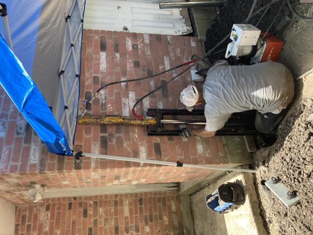 San Antonio, TX - We should be finishing up this foundation repair project today.  We installed 13 steel piers to stabilize this foundation. Here is one of our crew members using the hydraulic press to push the piers until they hit bedrock.