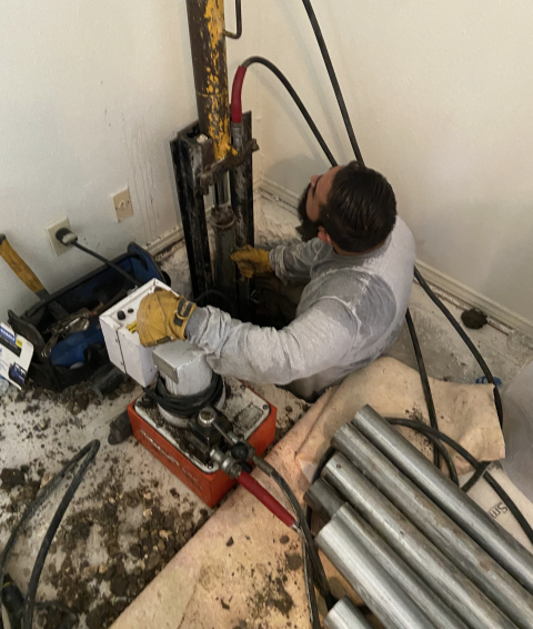 San Antonio, TX - We're close to finishing up this foundation repair project today. Here is the foreman using a hydraulic pump to push the steel piers into the ground until they hit resistance. This resistance will stabilize the foundation and then we'll lift sections if needed.