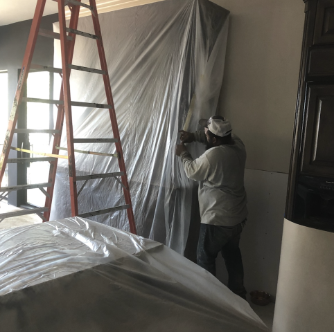Here is one of the crew members wrapping up the furniture before we do our interior breakouts. Drilling holes in the concrete to install these piers will get messy, so this is an extra step we are taking to help protect our customers belongings.