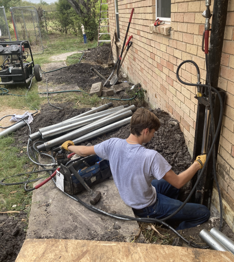 Here's one of our crew members getting our steel piers installed. You can see the piers to the left and right of him. The piers will be pushed into the ground until they hit bedrock or resistance to stabilize the foundation.