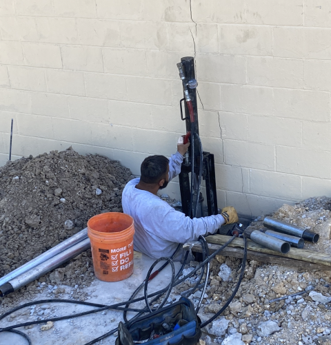 Working on a commercial foundation repair project. You can see the stair casing brick just in front of the foreman who is installing piers. This is one of 12 piers that will be installed to stabilize and lift this foundation and prevent further settlement.