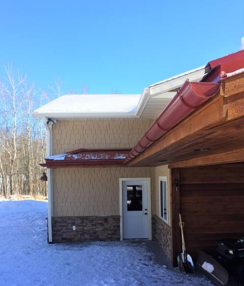 """Brainerd, MN - Custom Half Round gutters in Lighthouse Red, with standing seam snow stops on the steel roof. 25 year warranty even on steel roofs. The perfect accent for Eric's garage. With 6"""" K-style gutters above, made to handle all that Minnesota has to offer!"""