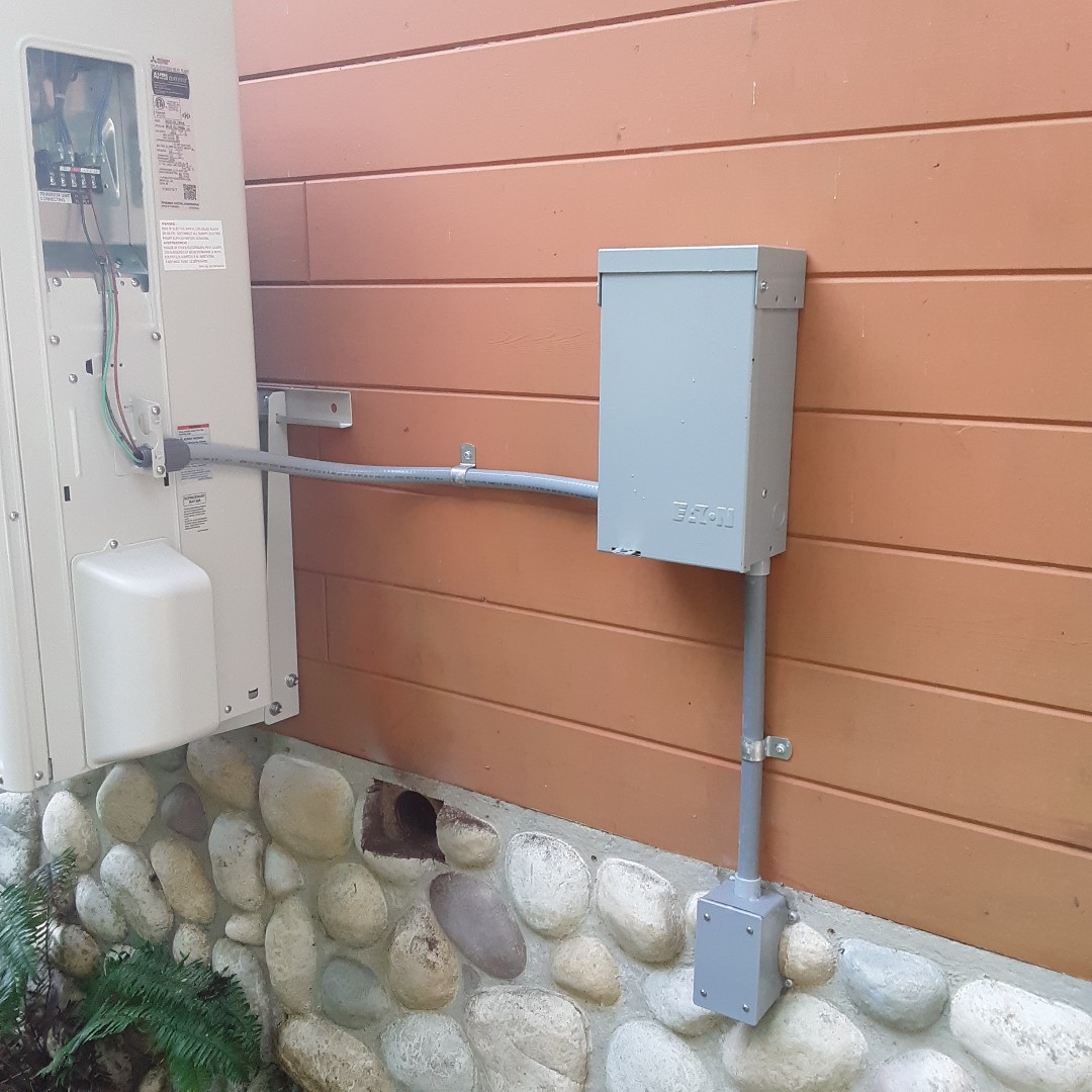 Granite Falls, WA - ELECTRICIAN installing a Eaton air conditioner disconnect with built in GFCI protected outlet in Granite falls