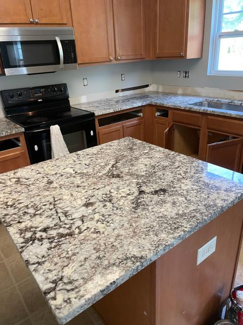 Raleigh, NC - kitchen countertop install. Bianca Spring granite. Island with overhang to accommodate bar stools.