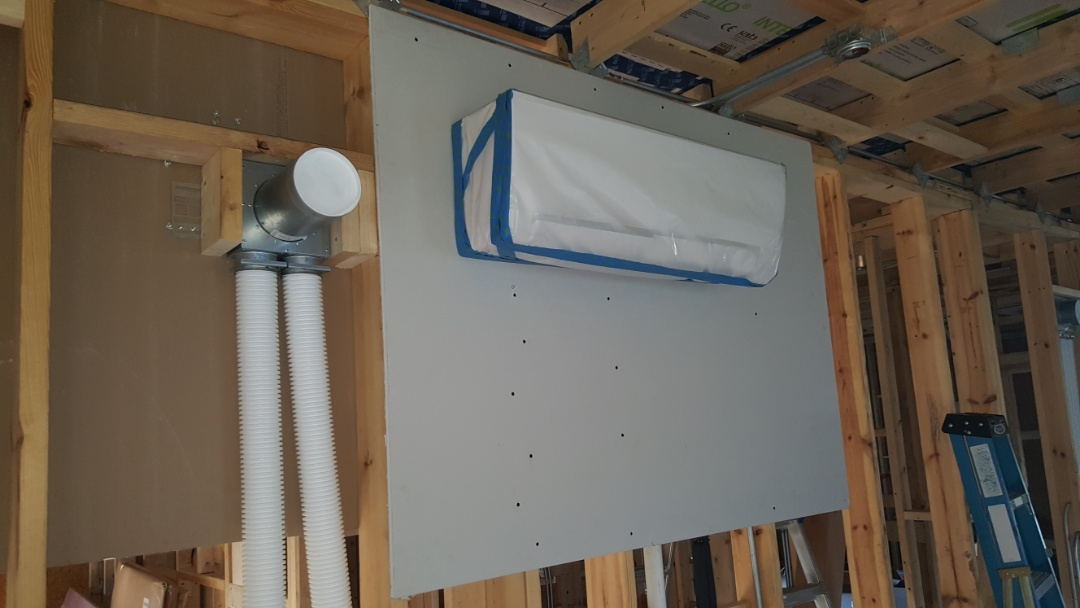 Palatine, IL - Wrapping Mitsubishi indoor units before wall coverings go up in Palatine, IL 60067 new construction Passive Net Zero home.
