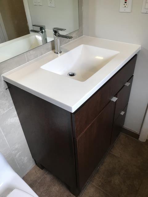 Highland Park, IL - New toilet and vanity cabinet equipped with a countertop and sink in a master bathroom.