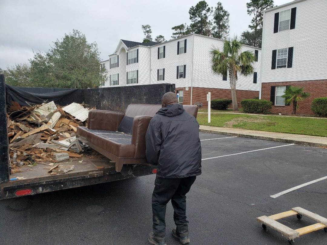 Removing old couch from apartment in Pensacola near University of West Florida and hauling it to landfill to properly dispose of it.
