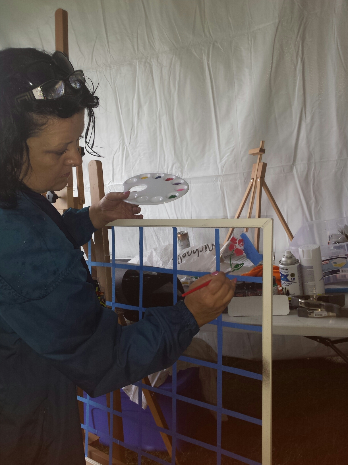 Spring, TX - Sherri is painting a flower on an Andersen window screen for children at The Woodlands Art Festival.