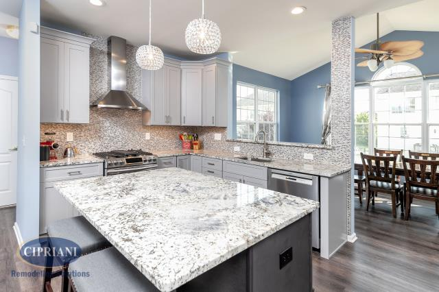 West Deptford, NJ - Our customer in West Deptford, NJ, came to us wanting to remodel their kitchen.  Melissa Firth came up with a beautiful kitchen design. She kept the same layout to keep the cost down and added white cabinets, light granite countertops, a new full-height range hood featuring tile access walls and backsplash. She increased the size of the island to give the homeowners more seating area in the kitchen. The wall color and flooring from the kitchen were brought into the dining area to tie both spaces together.