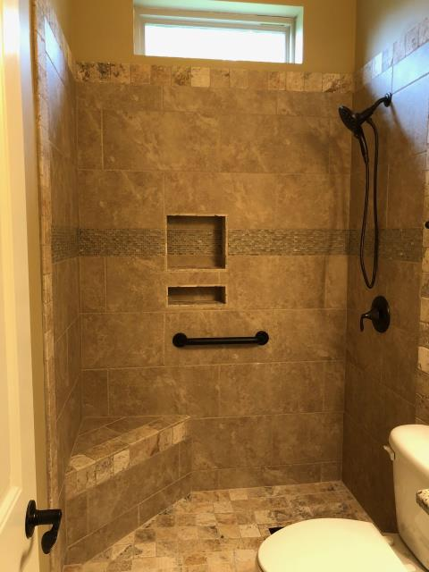 "Pensacola, FL - Replaced fiberglass tub and shower with new tile shower. Materials used on walls: Pietra D'Assis Noce with 4"" Picasso edge as accent. Feature strip from Happy Floor Project Deco glass and stone mosaics."