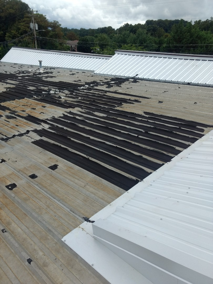 Johnson City, TN - Giving this business owner an estimate to fix the leak on the metal roof of this commercial building.