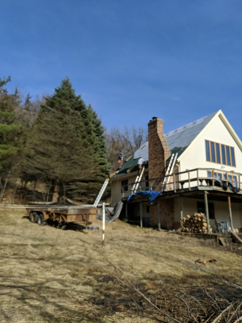 River Falls, WI - Reshingling an a-frame with Landmark CertainTeed hunter green shingles which are hard to find these days reflashing a chimney and putting new vents in