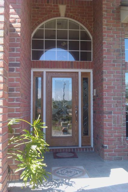 Installed large entry door with two sidelights and half round transom all impact fiberglass door Boise Cascade