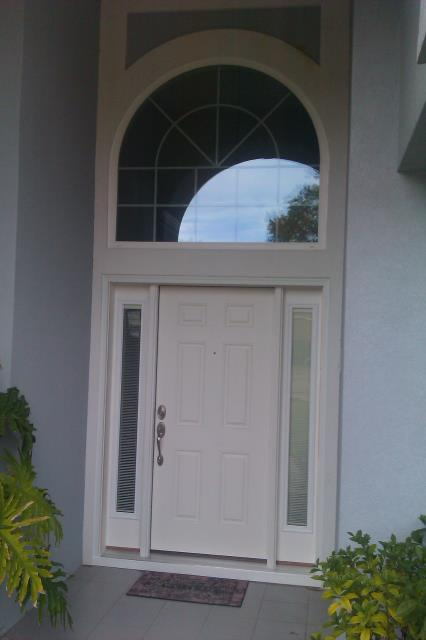 Navarre, FL - Large entry door with two sidelights and half round transom all impact fiberglass door Boise Cascade