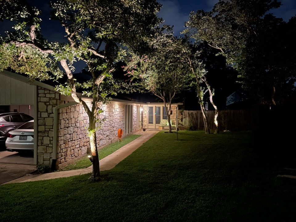 Austin, TX - Softly lit Great Hills area home, elegant soffit lighting, along with uplift tree canopies