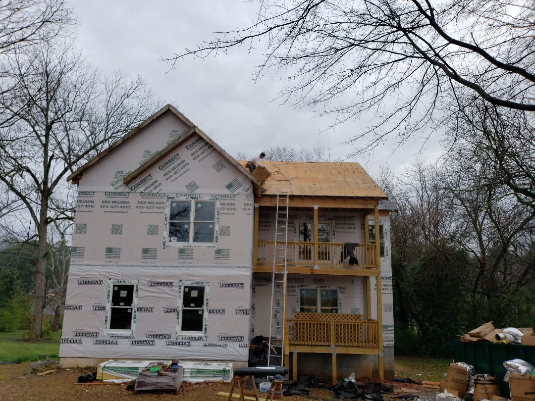 Marietta, GA - Flashing and installing synthetic underlayment underlayment to dry in a house being renovated ready for the siding to be installed
