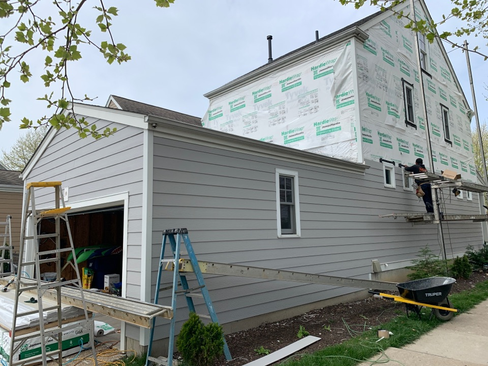 Saint Charles, MO - We are installing new James Hardie fiber cement lap siding and corner trim on this house in new town St. Charles, MO.   The client chose pearl gray siding with arctic white trim and is very happy to replace damaged hardboard siding.