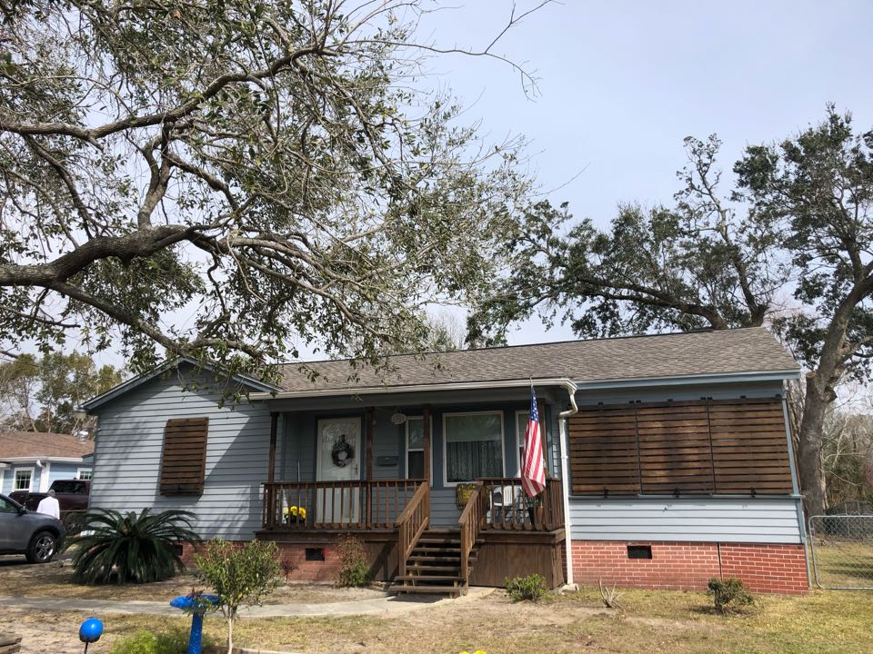 Gulfport, MS - This adorable one story cottage took roof damage during the wind gusts of hurricane Zeta. B&M Roofing was able to replace their old, damaged three tab shingle roof with a brand new GAF timberline HDZ architectural shingle in Weather wood.