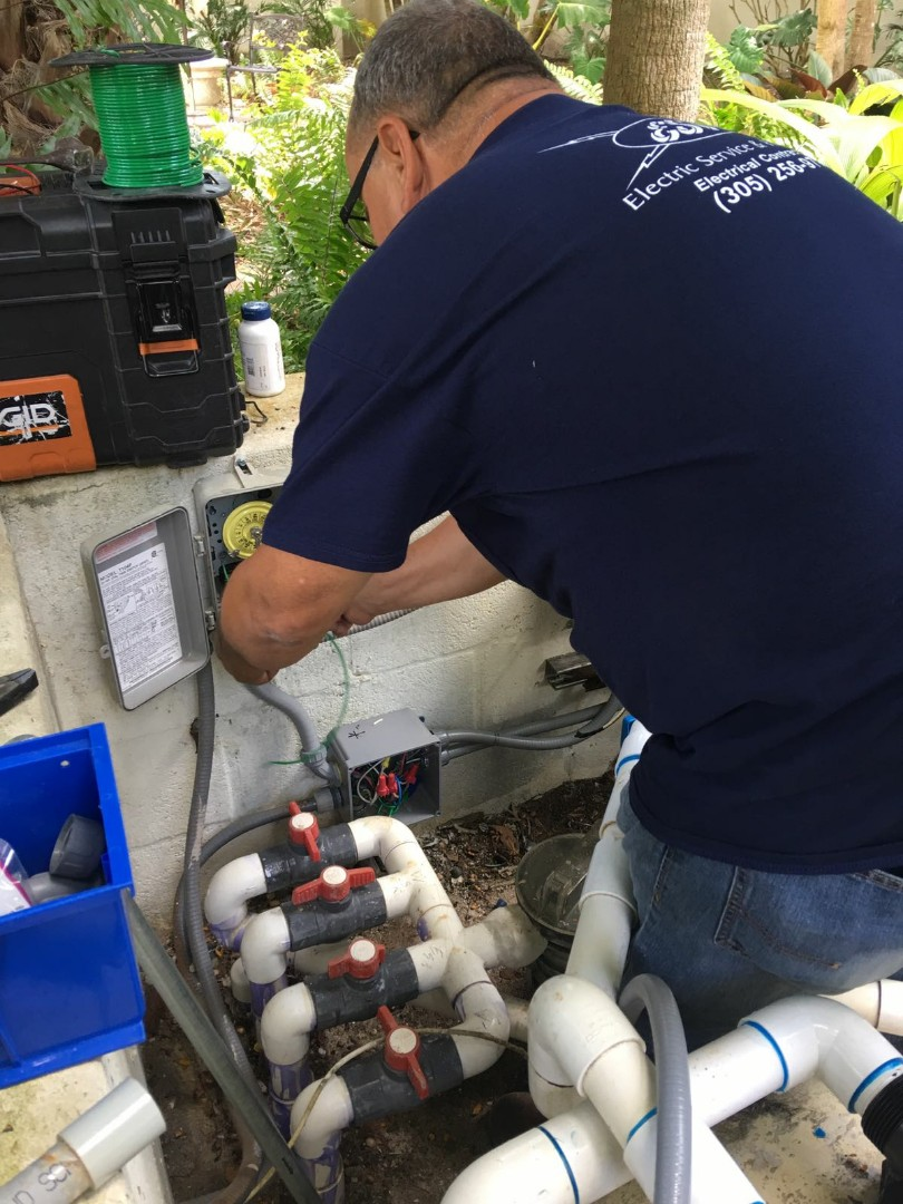 Licensed residential electrician making electrical upgrades to pool grounding, bonding and timer install in South Miami.