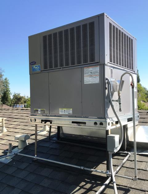 Fresno, CA - USA summer service of new Carrier package gas-electric unit on the roof.