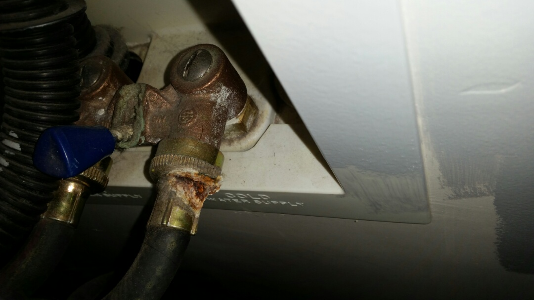 Centerville, UT - Water damage waiting to happen in Centerville, Utah. The picture shows corrosion on the hot water supply line to a washing machine. The corrosion is from a very small slow leak, but supply hoses don't last forever. Now would be a good time to replace it.