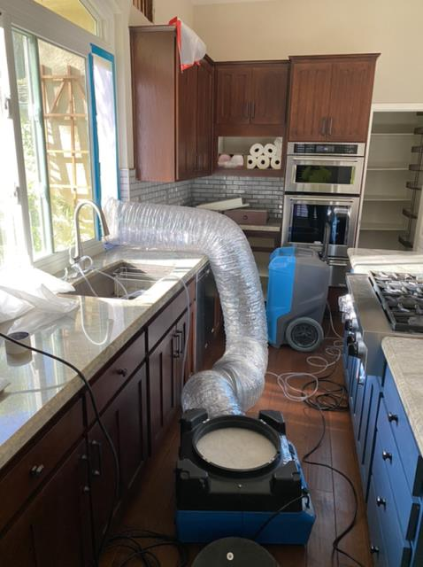 Escondido, CA - A hot water pipe burst upstairs. Caused damage to walls and kitchen cupboards, electrical, potential mold. Performed water damage mitigation and repair services to all areas affected.