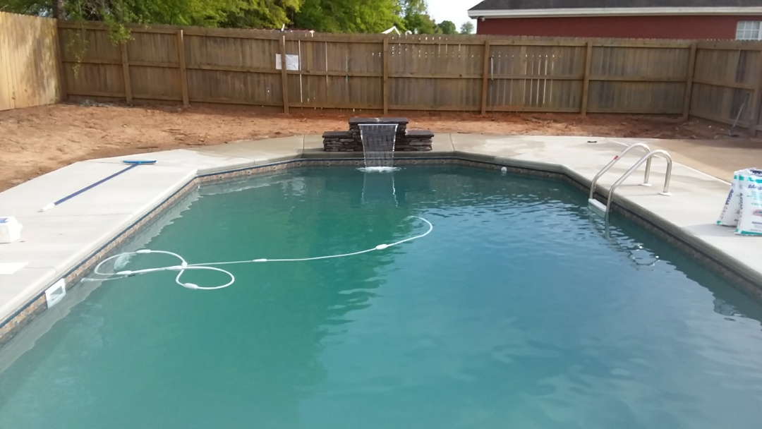 16x32 swimming pool installation with custom jump rock water fall.