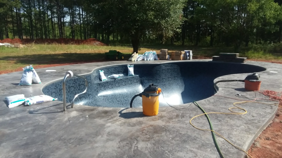 Valley Grande, AL - New 16x34 oasis pool installation with stamped concrete and jump rock waterfall.