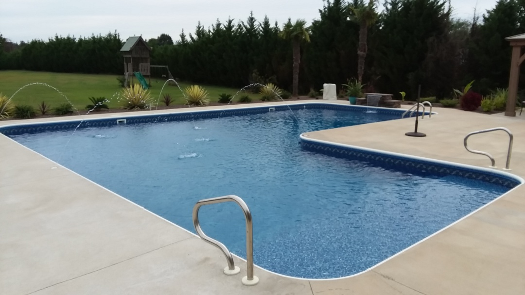 New true L swimming pool with deck jets and splash rock.