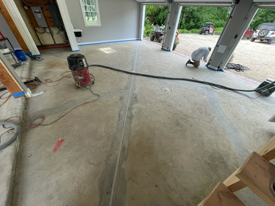 The crew is applying quick patch and cleaning up the surface before laying down the first coat on this concrete garage floor. Near Purcellville Virginia.