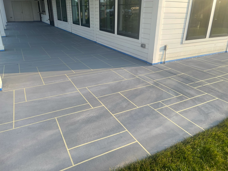 Design tape has been applied. The team will apply the stain coat of texture, remove design tape, stain the texture, and apply sealer. Near Leesburg Virginia