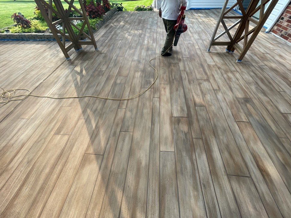 Stain has been applied. The team will apply sealer, remove protective tape, and the system will be complete.
