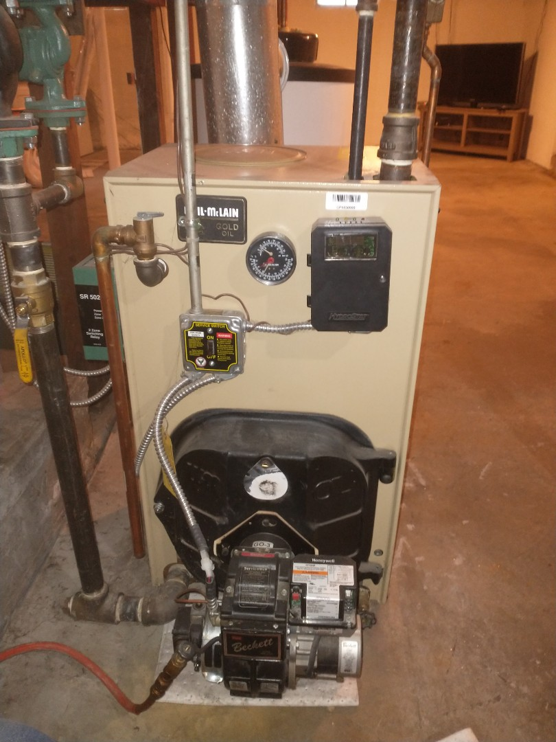 Performing annual maintenance on a Weil McLain oil boiler with a Beckett oil burner.