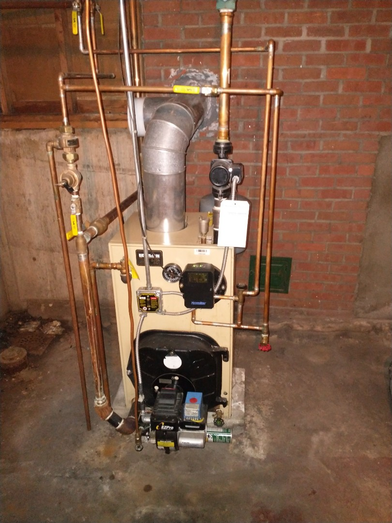 Performing annual maintenance on a Weil McLain oil boiler with a Carlin burner.