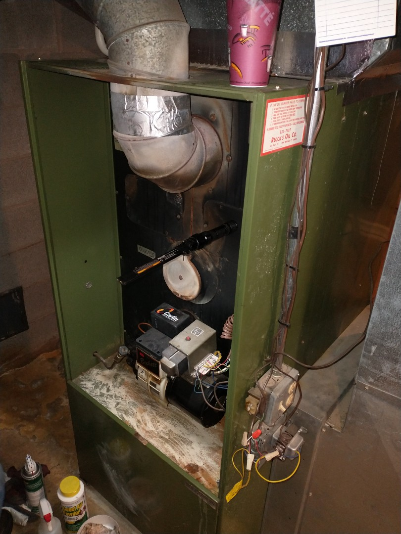 Performing annual maintenance on a Rheem oil furnace with a Beckett burner.