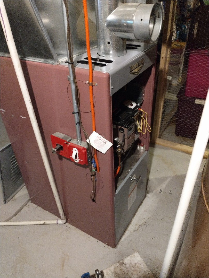 Performing annual maintenance on a Thermopride furnace with a Beckett oil burner.