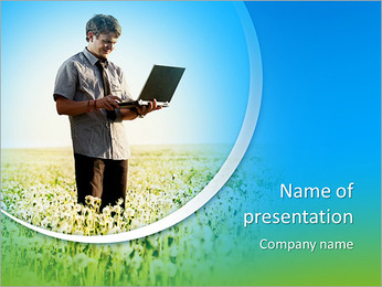 Happy young man with laptop in hand standing on meadow with dandelions PowerPoint Template