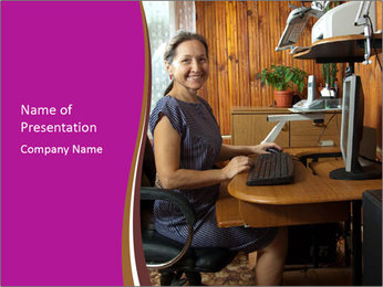 Girl smiling while sitting at a desk at the the computer. PowerPoint Template - Slide 1