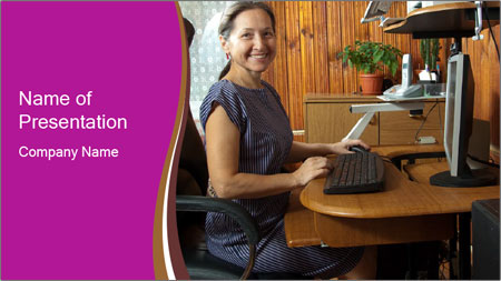 Girl smiling while sitting at a desk at the the computer. PowerPoint Template