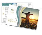 Young man standing on a meadow with dandelions on sunset sky background Postcard Templates